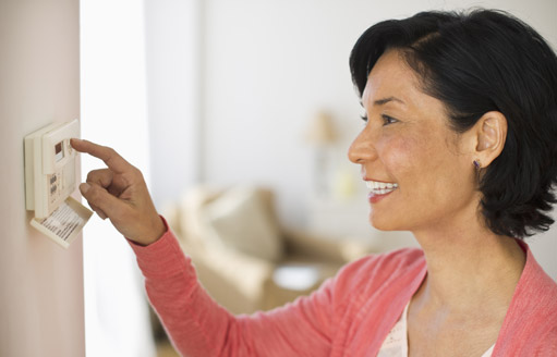 Premier AC & Heating LLC | Rock Hill, SC | smiling woman adjusting thermostat