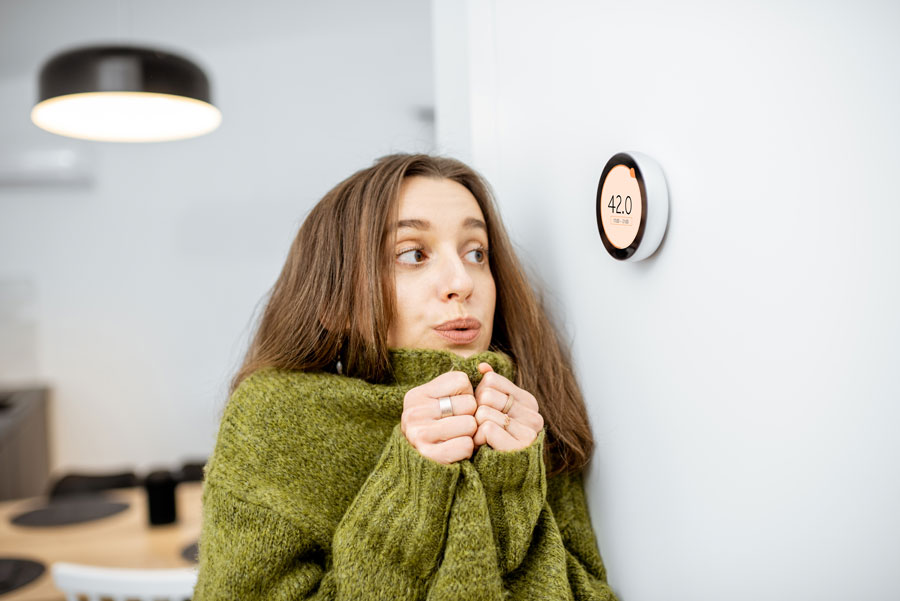 Premier AC & Heating LLC   Rock Hill, SC   young woman cold in her home, staring at thermostat